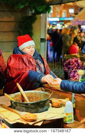 Woman Seller Of Sweet Almond At Christmas Market Night Riga