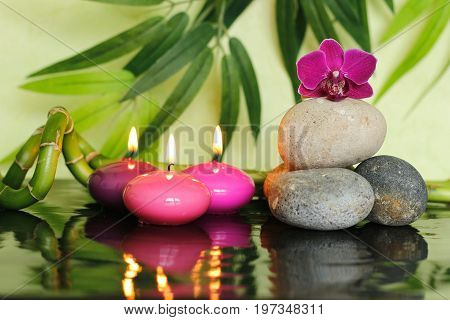 Pebbles arranged in Zen lifestyle on the right with an orchid at the top and pink candles lit