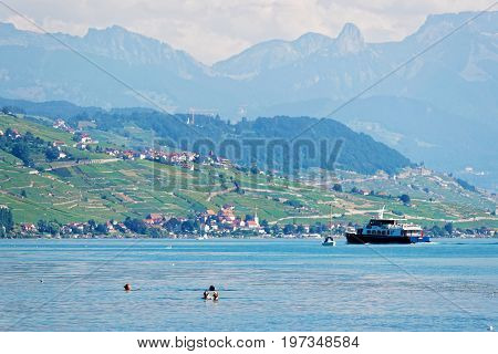Lausanne Switzerland - August 26 2016: People swimming and water ferry on Lake Geneva at Ouchy embankment in Lausanne Switzerland. People aboard