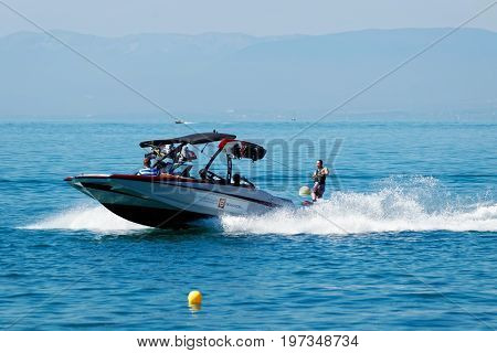 Motorboat With People Aboard And Man Wakesurfing On Lake Geneva