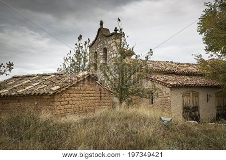 rustic houses made of wood and clay and a church in Navapalos, province of Soria, Spain