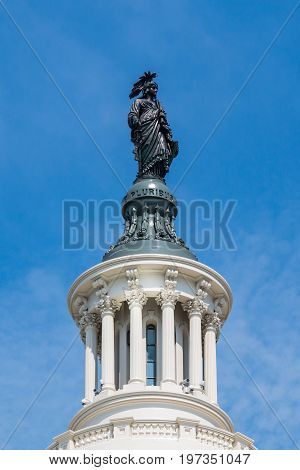 WASHINGTON, DC - JULY 12, 2017:  The Statue of Freedom, also known as Armed Freedom or Freedom, a bronze statue designed by Thomas Crawford and which crowns the dome of the U.S. Capitol building.