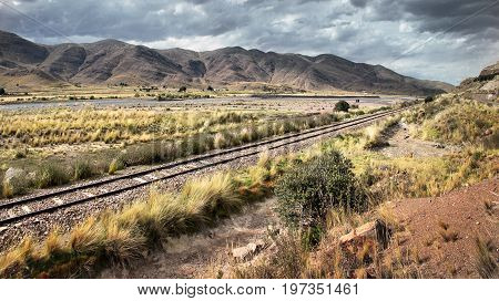 A railway track leading through the dry landscape of southern Peru