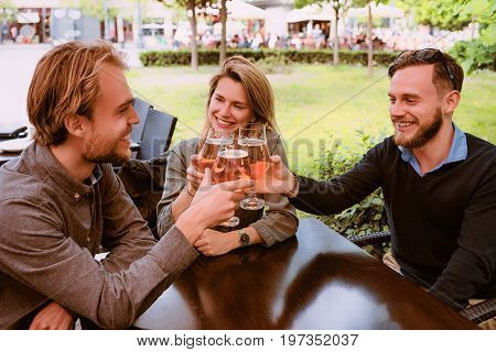 Group Of Smiling Young Friends Clang Glasses Of Beer