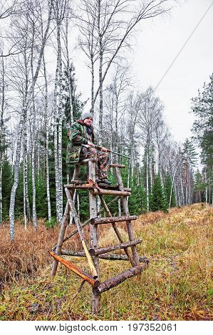 Male hunter at watch tower in autumn forest in Latvia Baltic country