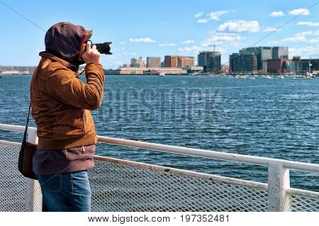 Man with camera at Charles river with the skyline of the city in the background in Boston America
