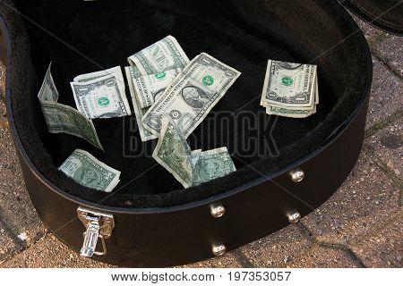 dollar bills tip money in black guitar case on city sidewalk