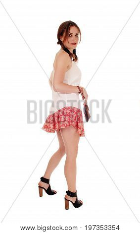 A beautiful young woman standing in profile looking back with a purse standing isolated for over white background