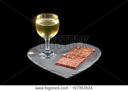 Love wine and chocolate. Luxury evening in with alchohol. Glass of white wine and bar of chocolate on slate heart platter. Isolated against black background with copy space.