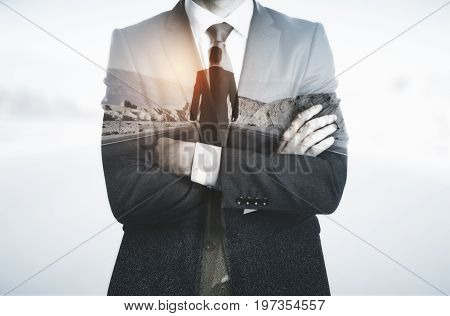Young businessman with folded arms thinking about way to success. Tomorrow concept. Double exposure