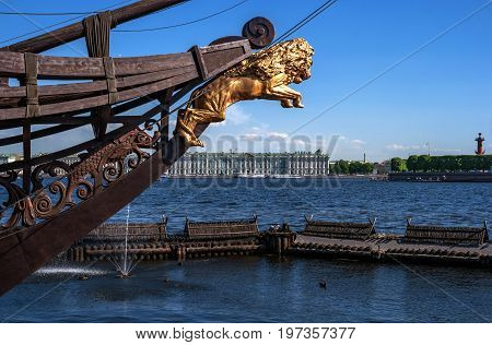 View of the Hermitage and the Rostral column on the opposite Bank of the Neva river in Sunny day. In the foreground bowsprit of a sailing ship with a Golden lion. Saint Petersburg, Russia.
