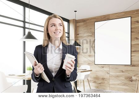 Blonde businesswoman with a cup of coffee and a copybook is standing in an office with wooden walls and panoramic windows. Poster. 3d rendering mock up