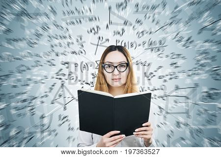 Portrait of an Asian woman wearing glasses and holding a huge open book. She is standing near a gray wall with formulas written on it. Mock up