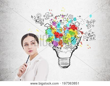 Portrait of a pensive young businesswoman wearing a white blouse and standing near a concrete wall with a business scheme inside a light bulb
