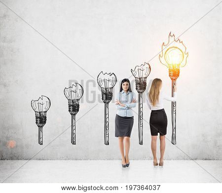 Portrait of two beautiful and smart business partners standing near a concrete wall. One is drawing a light bulb torch. The second is thinking. Toned image
