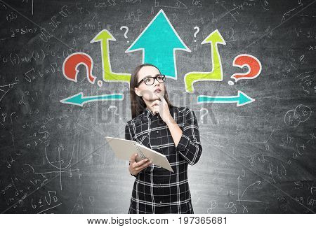 Nerd girl wearing glasses and a long checkered shirt is holding an open copybook and thinking while standing near a blackboard with colorful arrows and question marks on it.