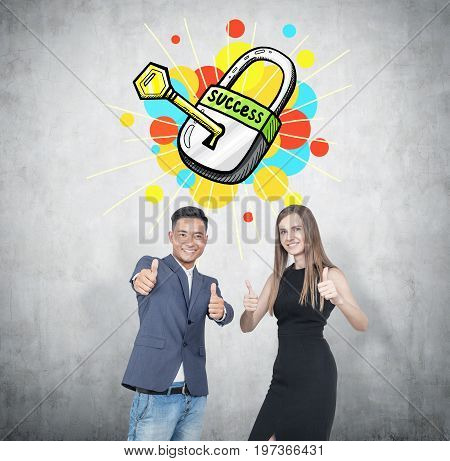 Asian businessman and his blonde colleague wearing an elegant black dress. They are showing thumb up signs and smiling. Concete background key to success sketch.