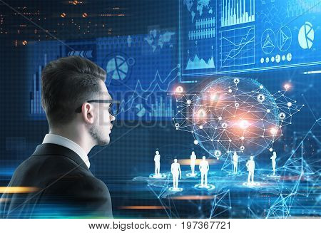 Side view of a young trader wearing glasses looking at an Earth hologram and a bunch of infographics in a futuristic surrounding. Toned image double exposure.