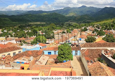 bird eye view at Trinidad Cuba. There are red tile roofs below and mountains in the background