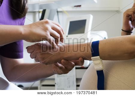 Nurse putting an IV needle into a patients hand