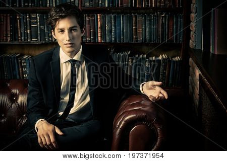 Handsome well-dressed young man by the bookshelves in a room with classic interior. Business style.