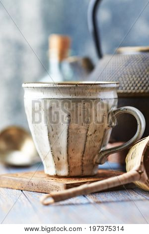 Close up of a ceramic mug and wooden tea strainer