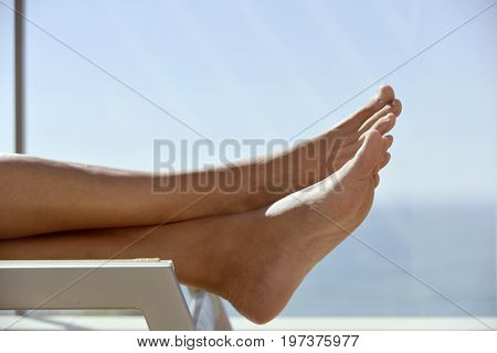 closeup of the feet and legs of a caucasian man relaxing lying down on a sunlounger in a terrace