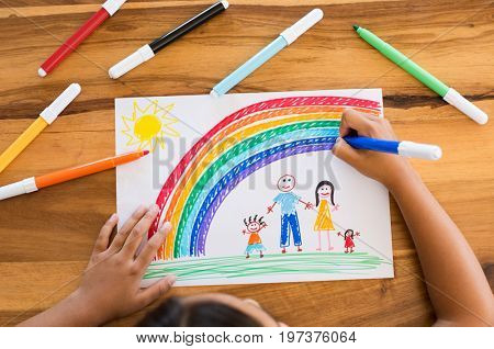Top view of little girlâ??s hands painting happy family with marker on white paper. Drawing sheet with artwork by daughter on table. Little girl using marker to make family painting with rainbow.