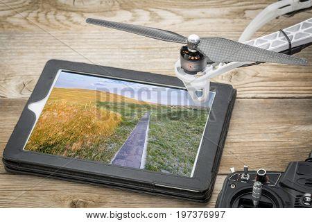 Narrow, one lane road in Nebraska Sandhills, reviewing aerial image on a digital tablet