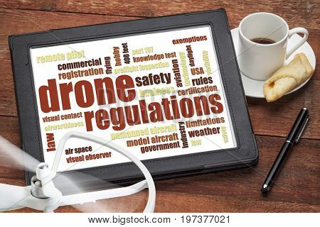 drone regulations (USA related) word cloud on a digital tablet with a cup of coffee and rotating propeller