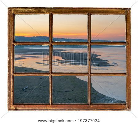 sunrise over river in Nebraska Sandhills as seen through a vintage, grunge, sash window with dirty glass