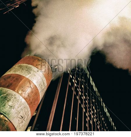 steam escaping from a vent in the street, New York City, night time