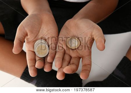 Hands of little boy with coins, closeup. Poverty concept