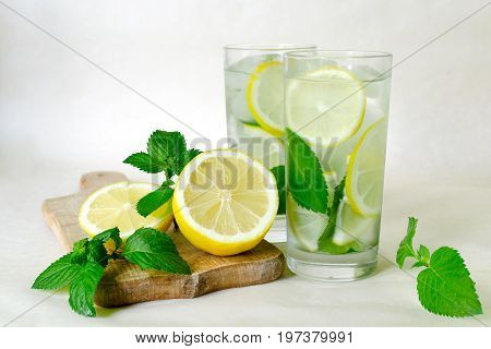 Lemon mint detox water. Home-made lemonade with mint lemon and ice in glasses on a light background. Wooden board sliced lemon and mint leaves
