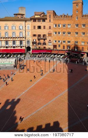SIENA ITALY - March 14 2014: The shadow of Torre del Mangia in Piazza del Campo the principal public space of the historic center of Siena.