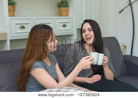 Beautiful Girls With Friend Talking And Holding Coffee Cups In Living Room At Home