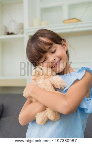Child Girl Playing With Teddy Bear In Living Room At Home