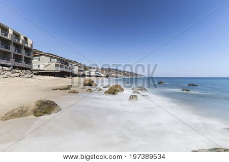 Malibu beach homes with motion blur surf near Los Angeles in Southern California.