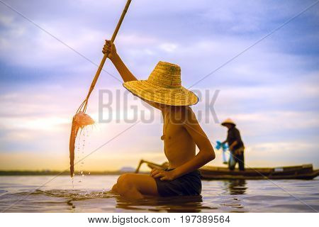 Children Fisherman boy with catching fish and fisherman throwing nets on boat on lake river thailand