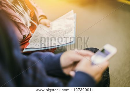 Closeup Hand Of Two Tourist With Map And Searching Location In Smartphone Shallow Depth Of Field.
