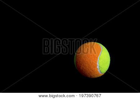one tennis ball on a black background