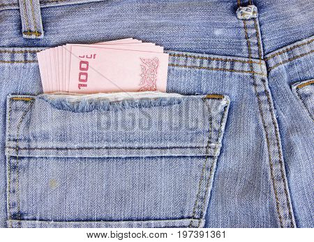 Thailand money including 100 baht in back pocket of a man's black charcoal jeans pocket