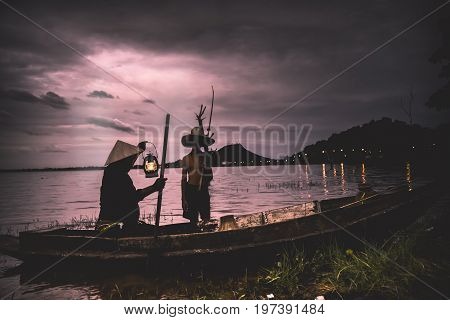 Children Fisherman boy with catching fish and fisherman holding lamp on boat on lake river thailand