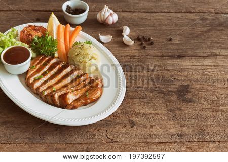 Barbecue pork steak slices on white plate. Delicious pork steak for lunch or dinner on wood table. Moist and soft homemade pork barbecue served with mash potato barbecue sauce and vegetable. Slices pork steak with barbecue sauce on table.