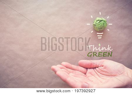 Green paper light bulb with Think Green over hands eco energy saving concept