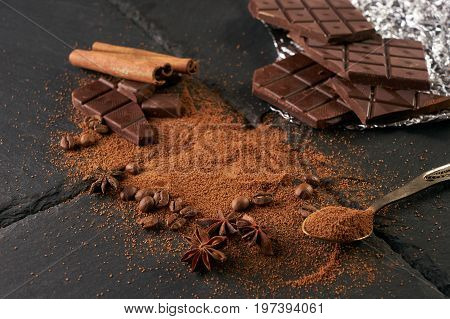 Cocoa and coffee beans vintage spoon with cocoa powder cinnamon sticks and broken chocolate slices on a dark slate background