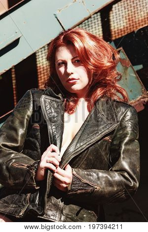 Confident, sexy woman with red hair only with an old leather jacket clad in front of a conveyor belt