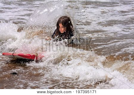 A little girl falls off a boogie board in shallow water as a wave breaks on her back throwing a spray of water into the air.
