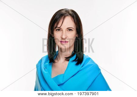 Attractive young brunette woman covered by blue shawl