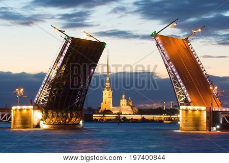 Peter and Paul Cathedral in the alignment of the diluted Palace Bridge on a white night. Saint-Petersburg. Russia
